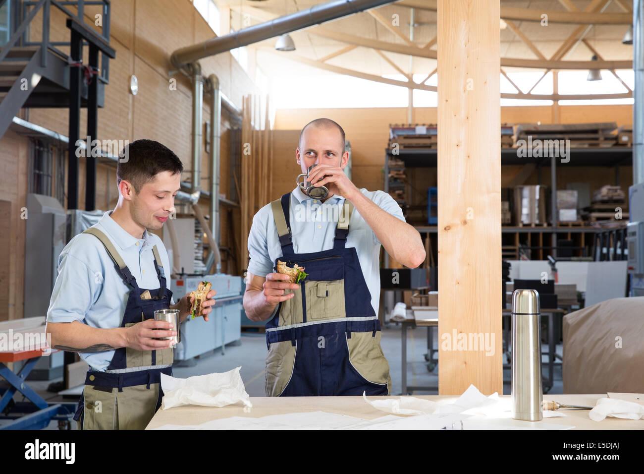 Handwerker in Werkstatt mit Frühstückspause Stockbild