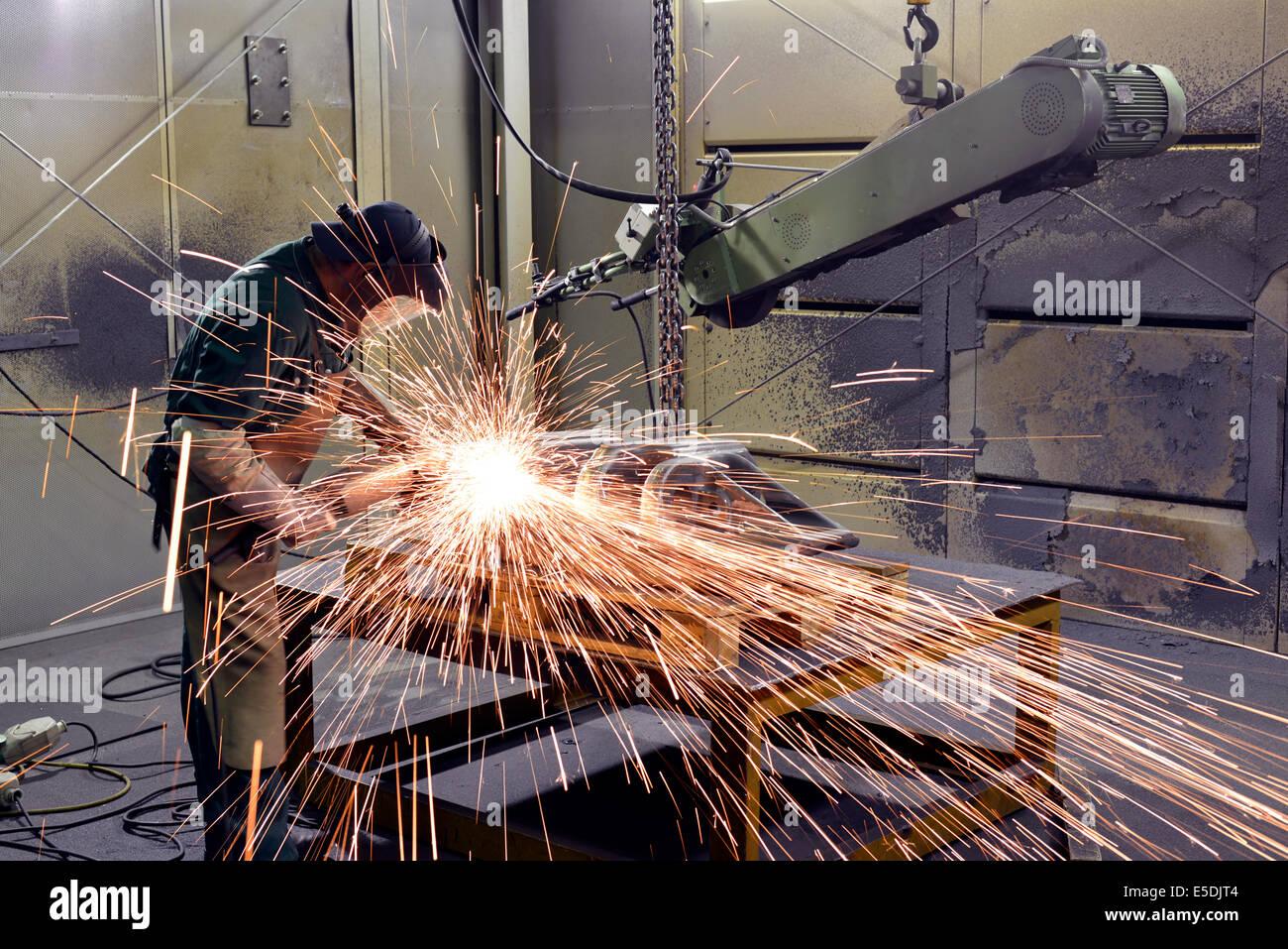 Arbeiten mit der Schleifmaschine in einer Gießerei Stockbild