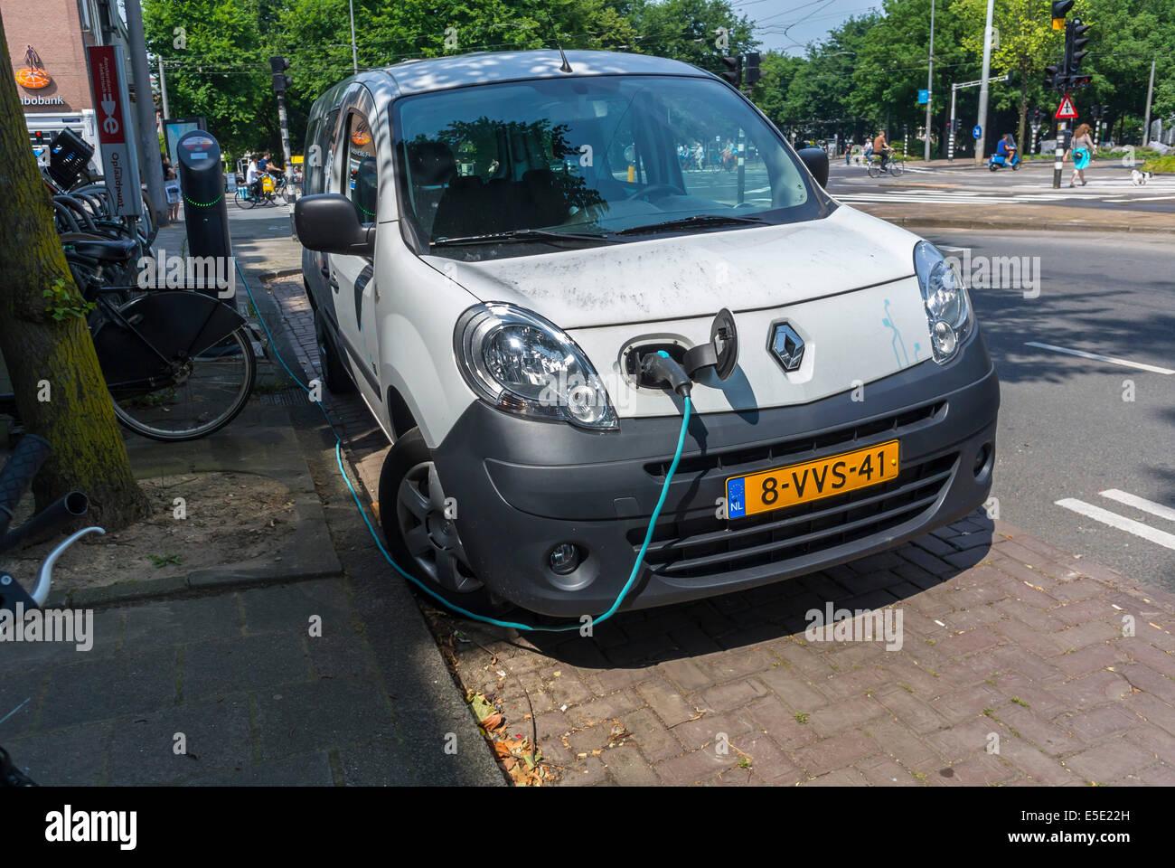 Amsterdam, Holland, Niederlande, Green Car, Elektroauto aufgeladen auf Straße mit Kabel Stockbild