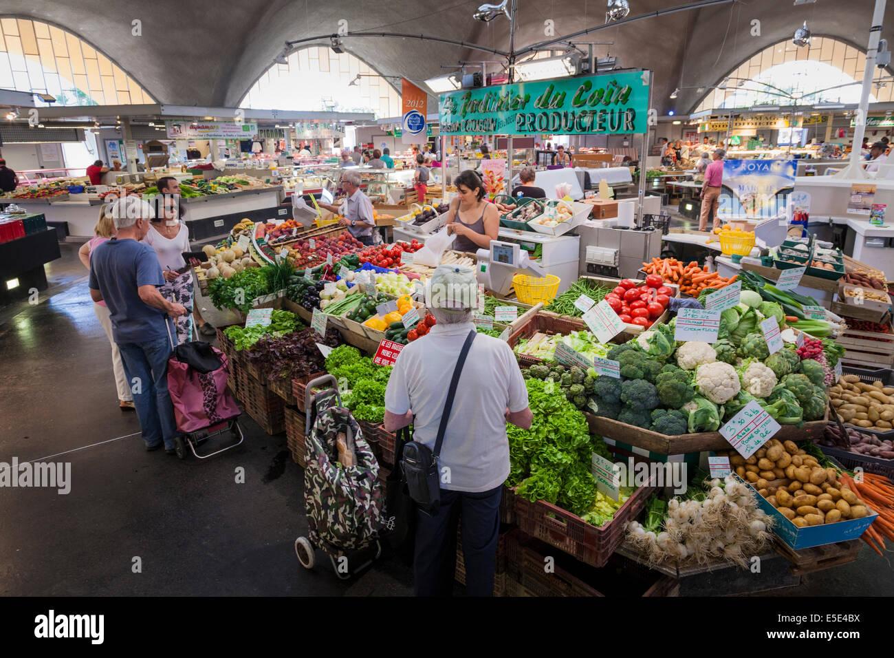 Kunden kaufen Obst und Gemüse im Inneren der Markthalle in Royan Frankreich. Stockbild