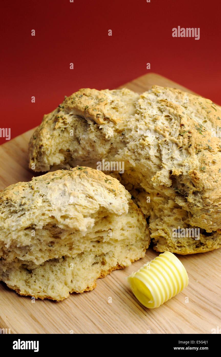 Australische traditionelle Bier Teig Dämpfer Brot mit Butter auf Brot Brett gegen einen roten Ocker Hintergrund Stockbild