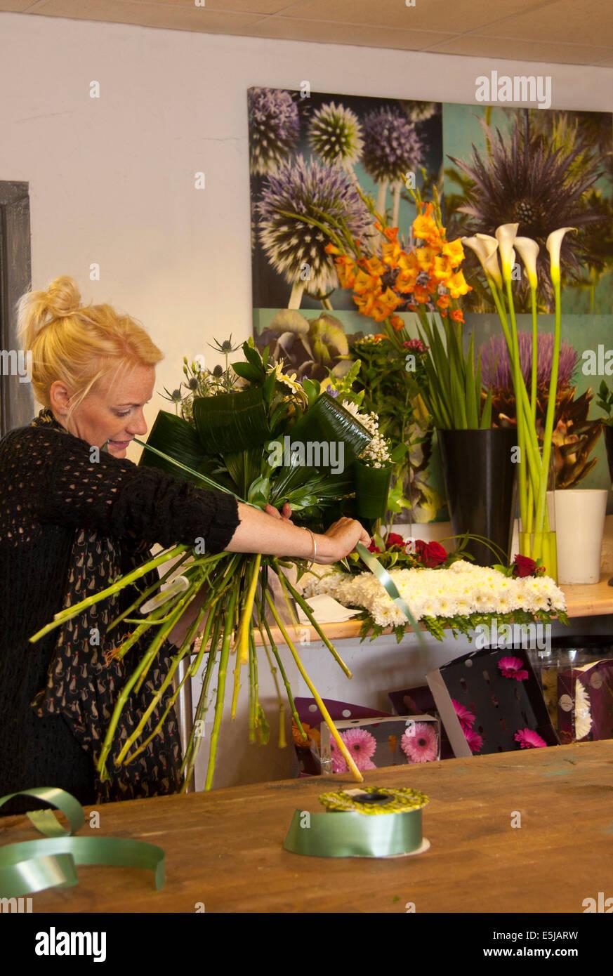 floristen arrangieren einen gebundenen blumenstrau in einem blumenladen mit trauben von blumen. Black Bedroom Furniture Sets. Home Design Ideas