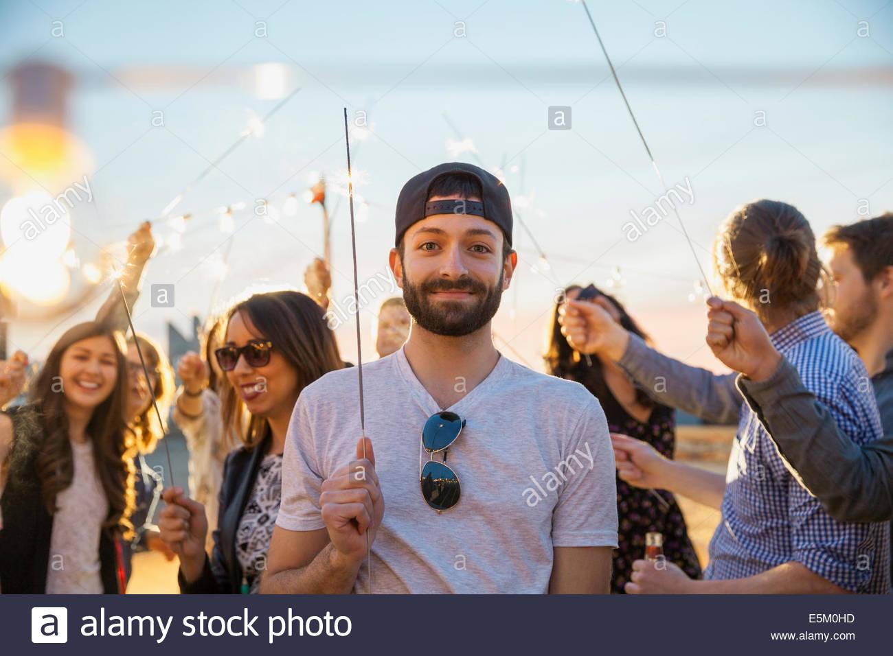 Porträt von lächelnden Mann mit Wunderkerze auf party Stockbild