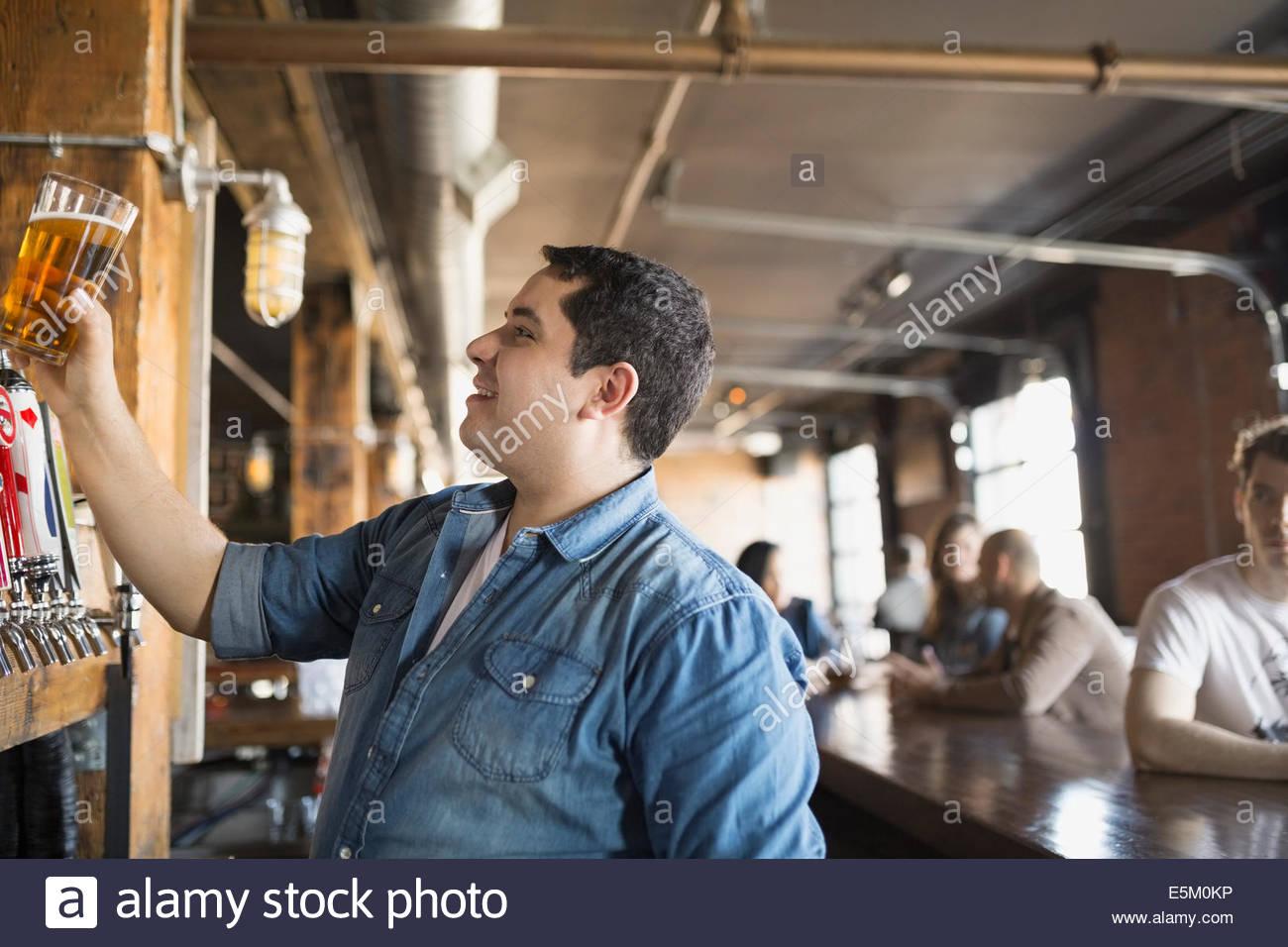 Barkeeper beäugte Pint Bier Stockbild