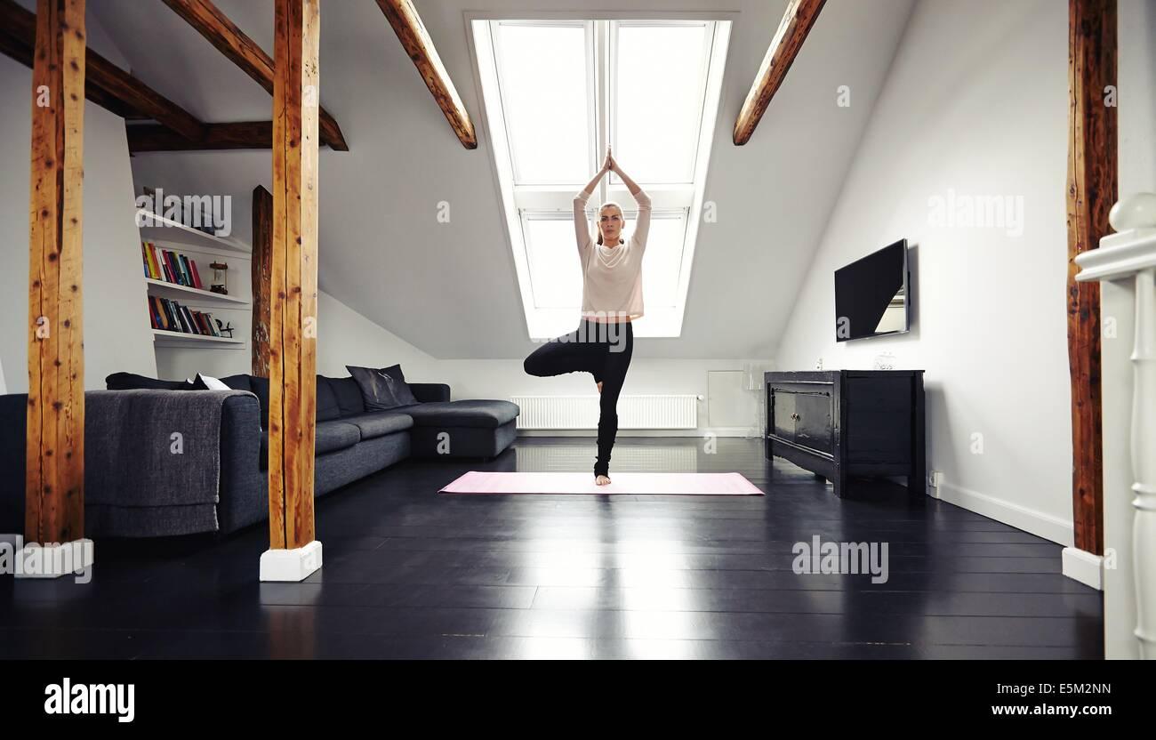 Junge hübsche Brünette stehen und Training zu Hause. Passen Sie Weibchen in Baumpose beim Yoga im Wohnzimmer. Stockbild