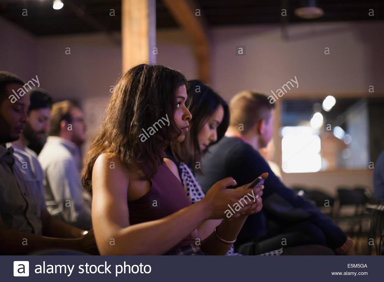 Frau im Publikum Check-Handy Stockbild