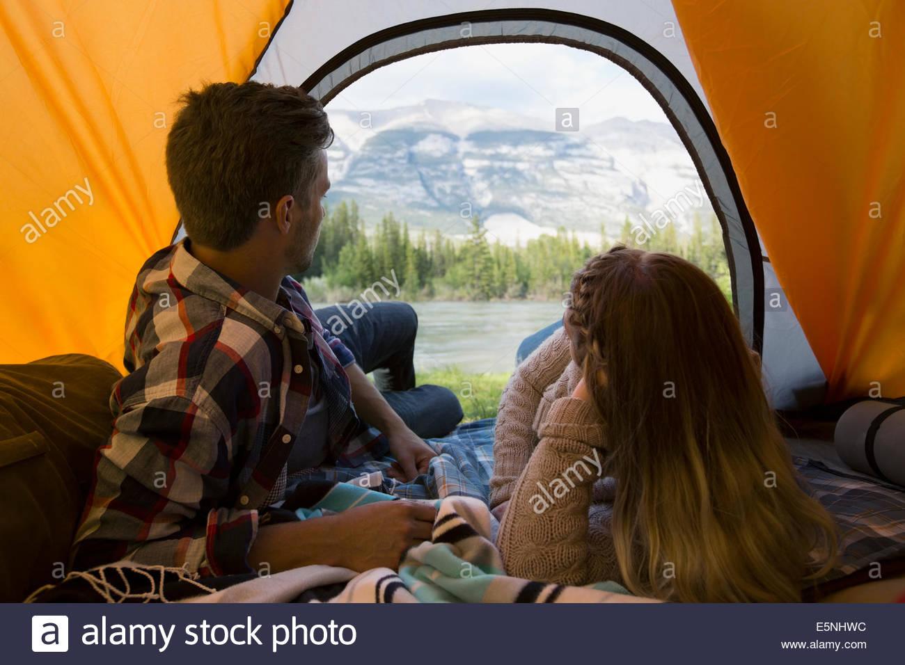 Paar im Zelt und Blick auf Berge Stockbild