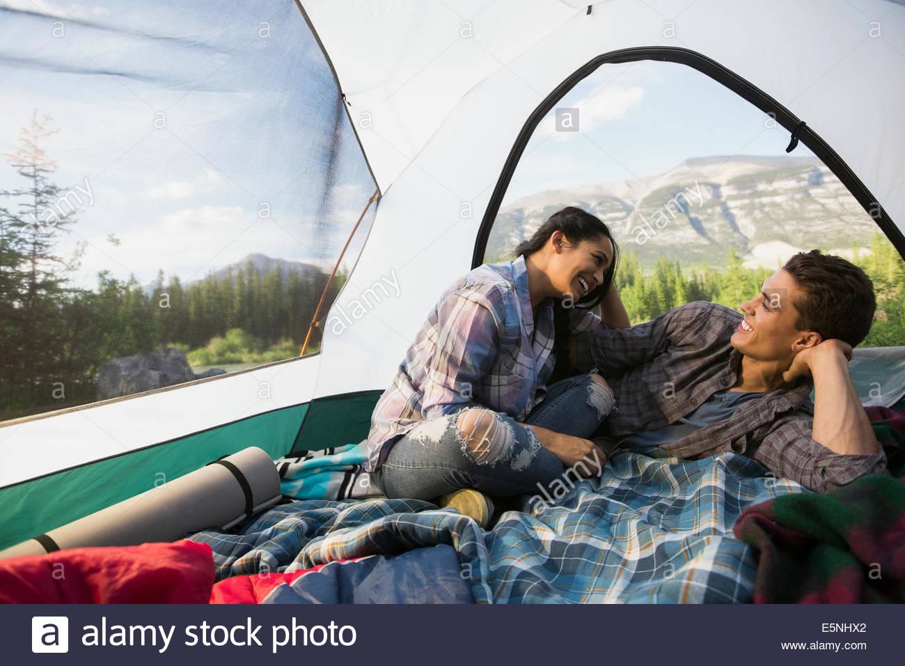Paar sprechen im Zelt mit Blick auf die Berge Stockbild