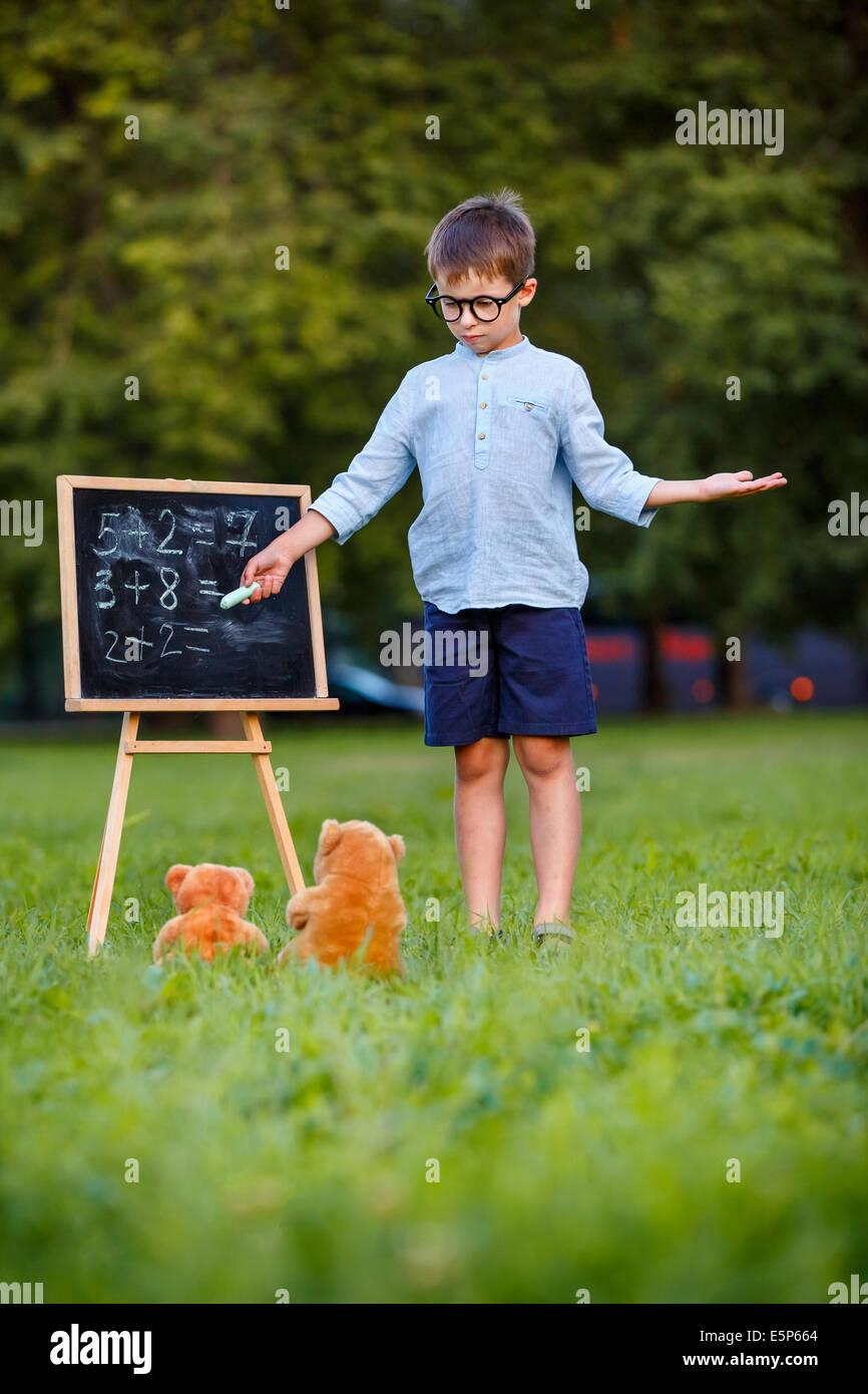 Niedliche kleine Schüler lehren seine Spielzeuge im freien Stockbild