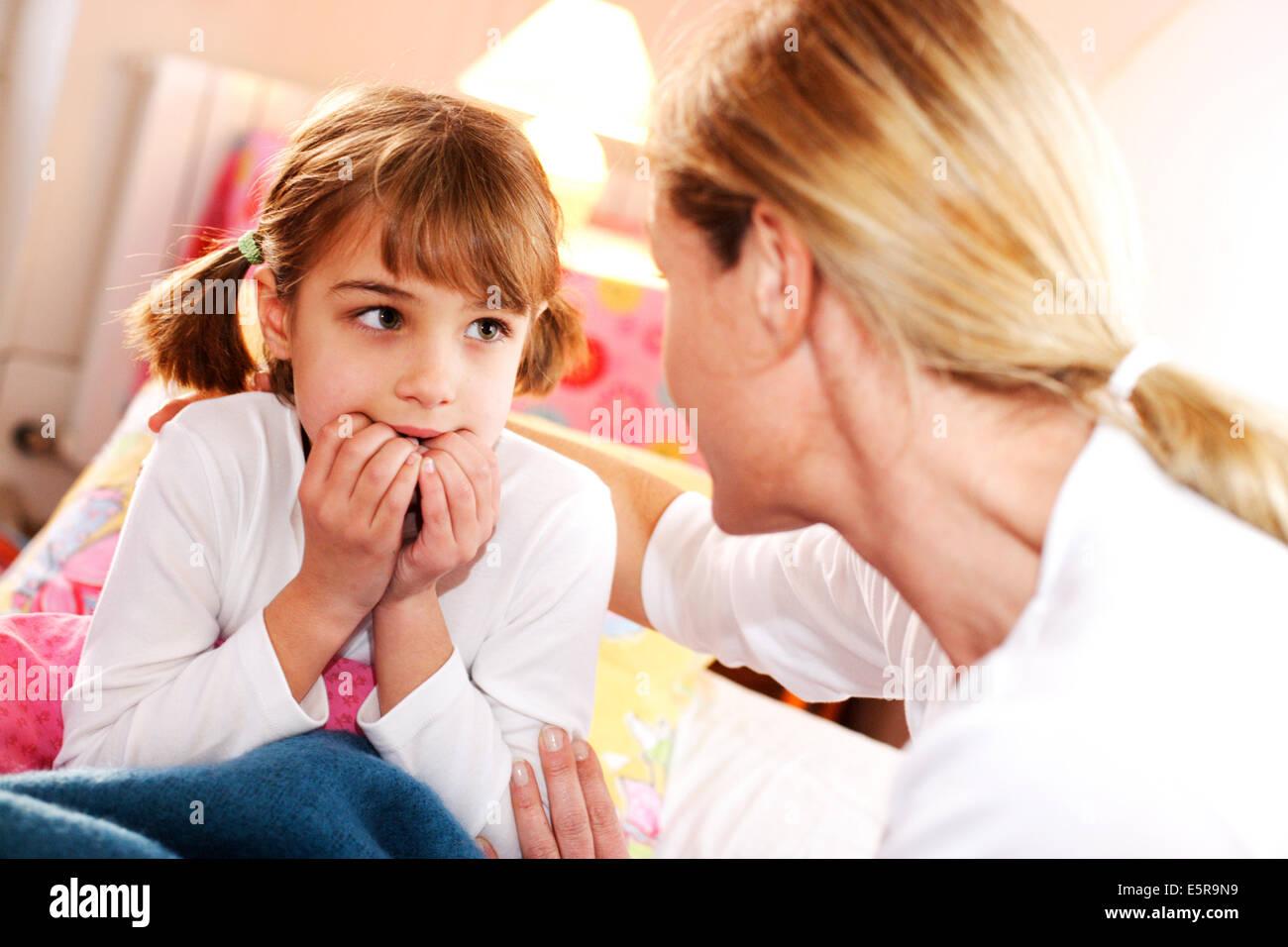 Mutter im Gespräch mit ihrem 7-jährigen Mädchen im Bett in der Nacht. Stockbild