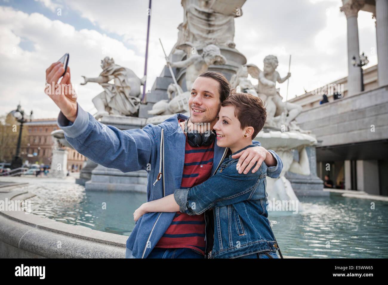 Junge Erwachsene paar unter Bild von sich selbst, Wien, Österreich Stockbild