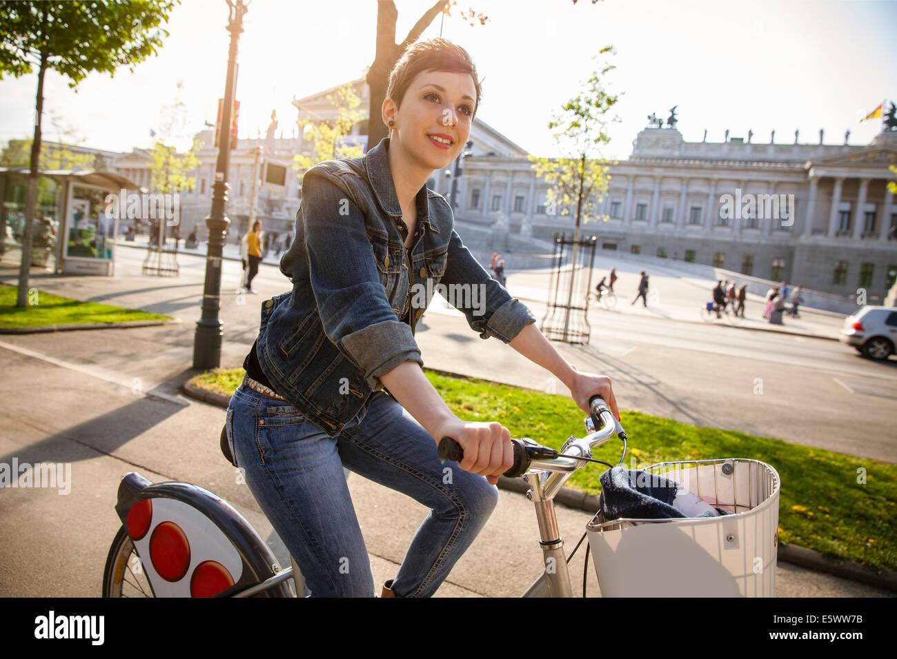 Junge Frau Radfahren durch City, Wien, Österreich Stockfoto