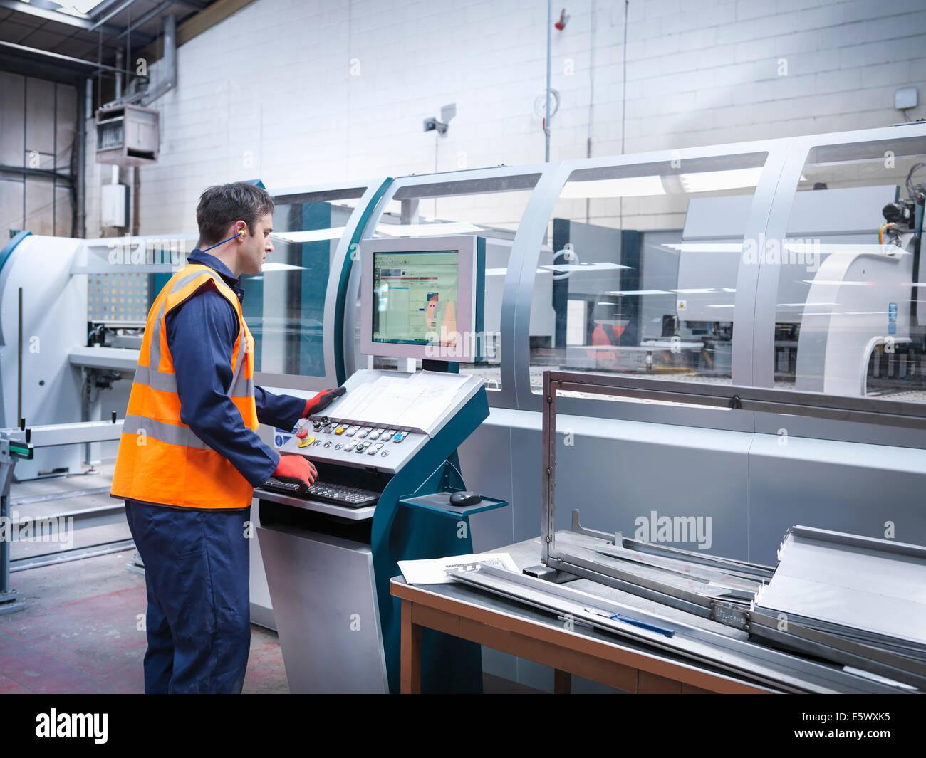Arbeiter mit Roboter-Metall-Schneidemaschine in Blech-Fabrik Stockbild