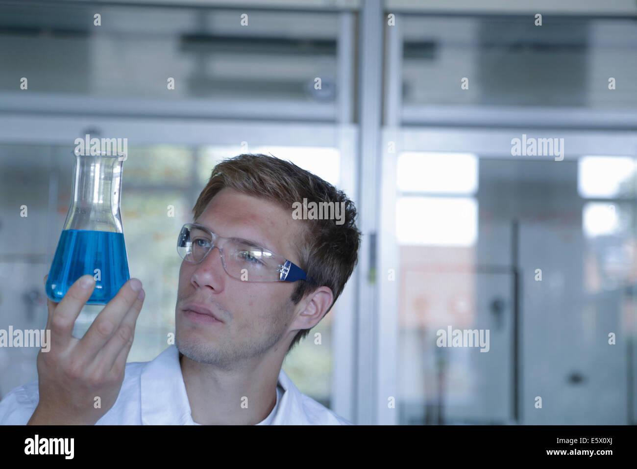 Junge männliche Wissenschaftler hält Erlenmeyerkolben im Labor Stockbild
