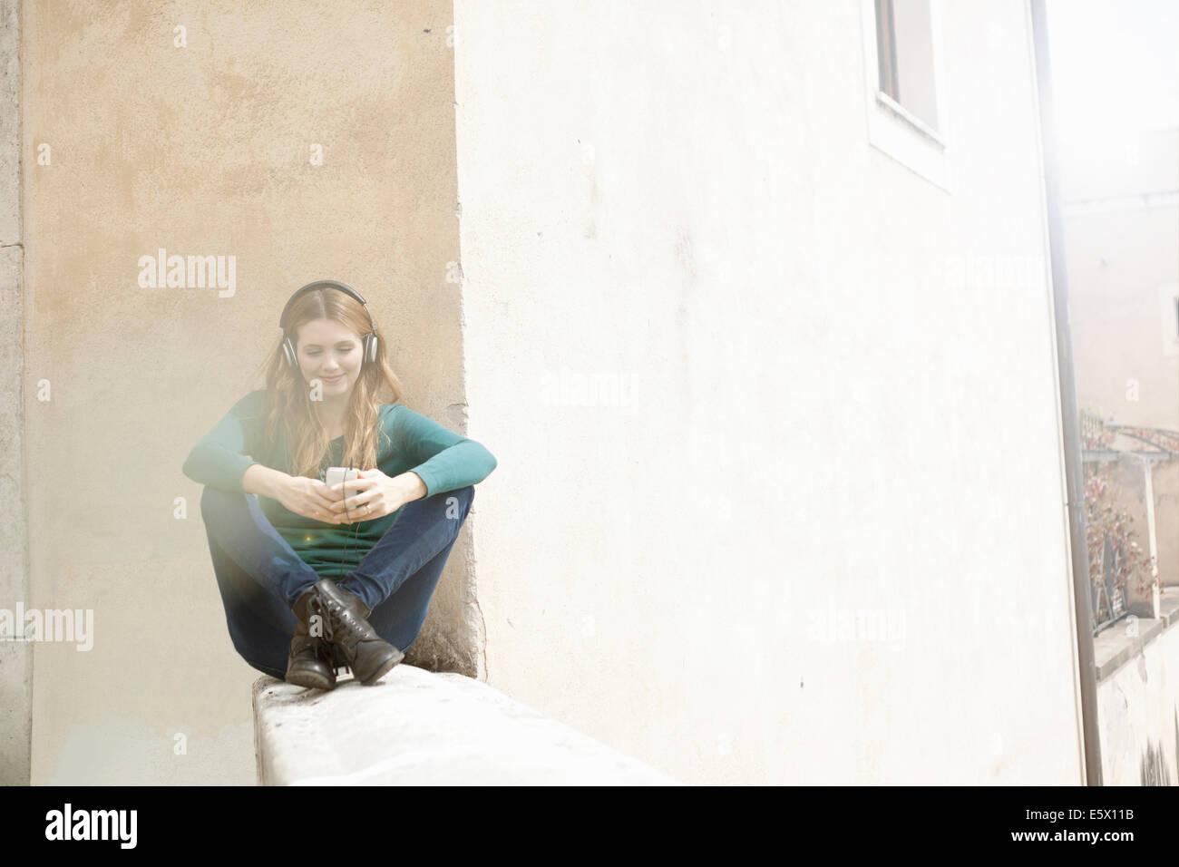 Junge Frau sitzt cross legged anhören von Musik über Kopfhörer Stockbild