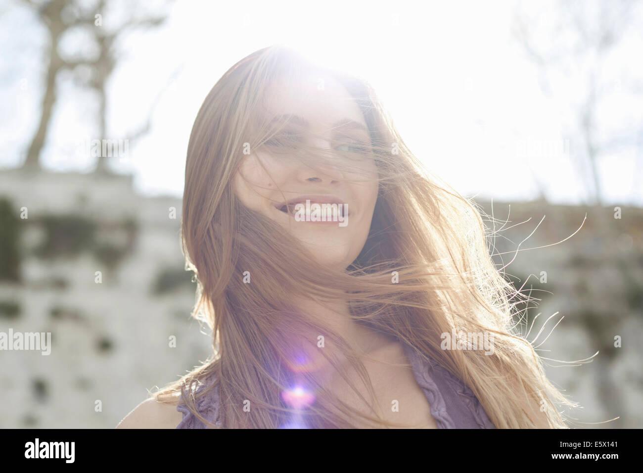 Glückliche junge Frau im Sonnenlicht, Haar weht über Gesicht Stockfoto