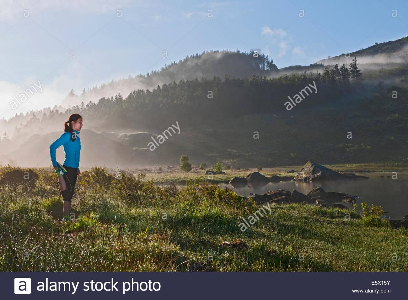 Weibliche Läufer erstreckt sich vom See, Capel Curig, Snowdonia, North Wales, UK Stockbild