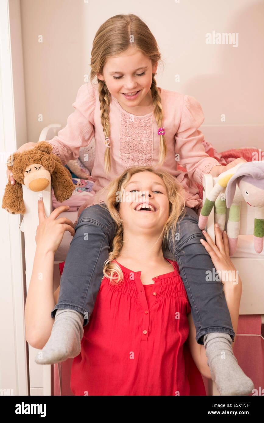 Mädchen lacht, während Schwester eine Schulter fahren im Schlafzimmer Stockbild