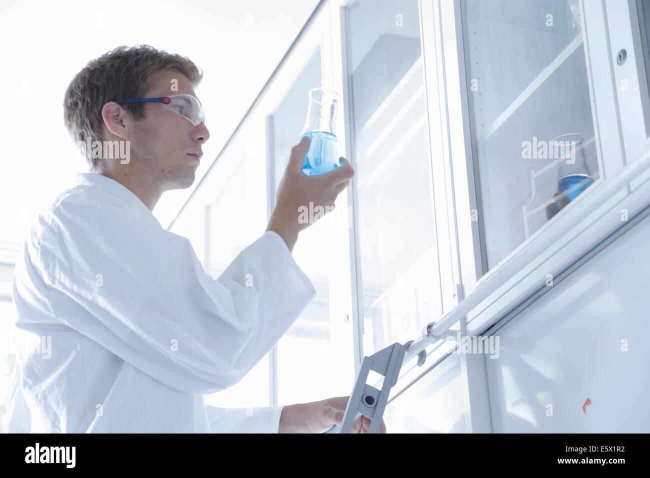 Männliche Wissenschaftler hinterfragen Erlenmeyerkolben im Labor Stockbild