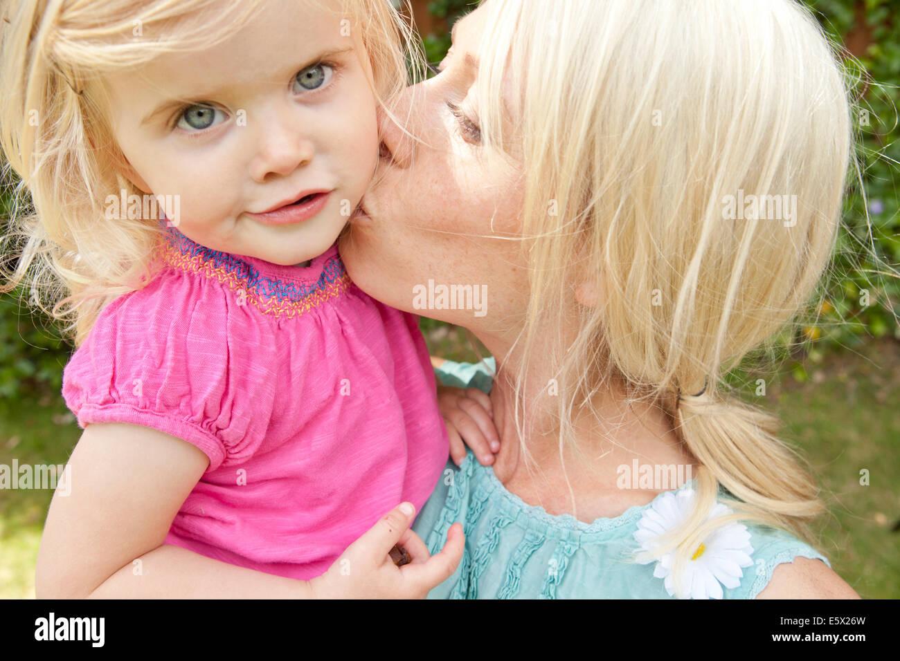 Nahaufnahme eines jungen Erwachsenen Mutter küssen Kleinkind Tochter im Garten Stockbild