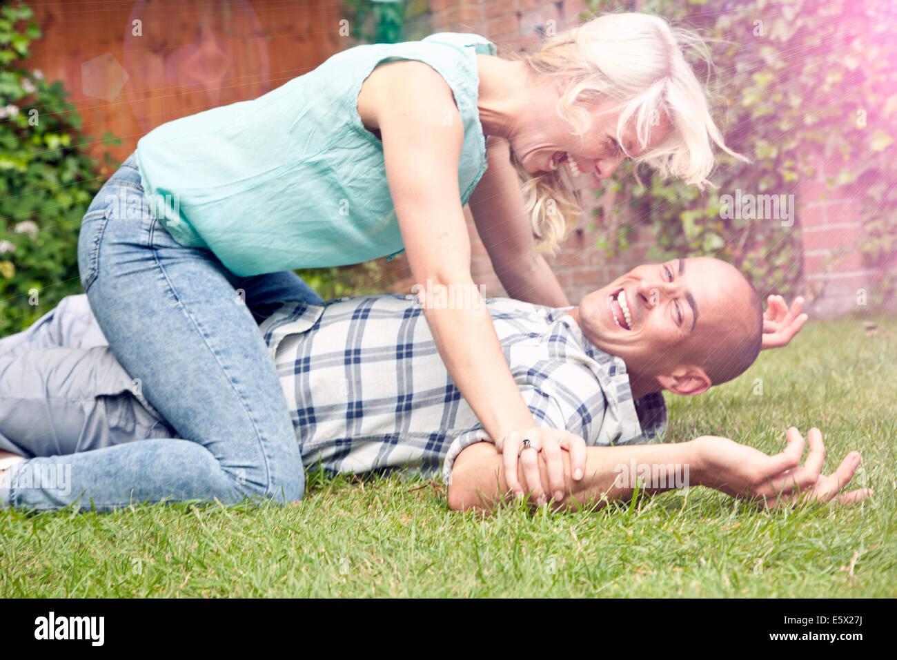 Glückliches Paar spielen kämpfen im Garten Stockbild