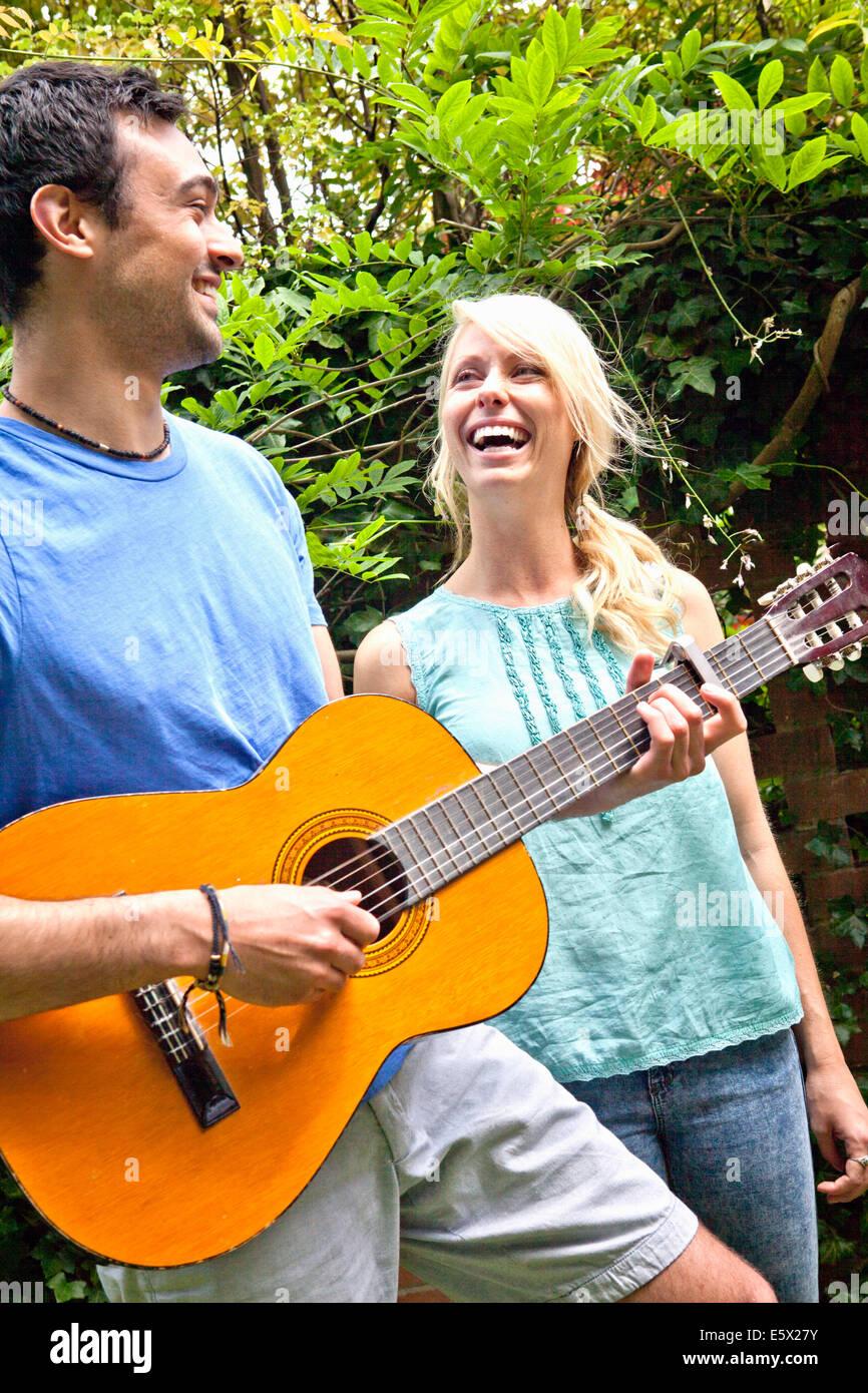 Junger Mann spielt akustische Gitarre im Garten für Freundin Stockbild