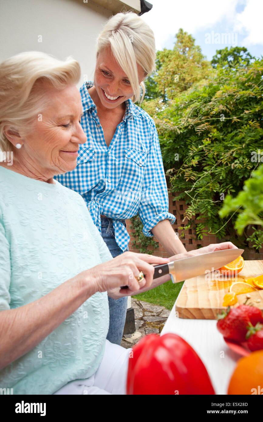 Großmutter und Enkelin im Chat während der Zubereitung von Speisen am Gartentisch Stockbild