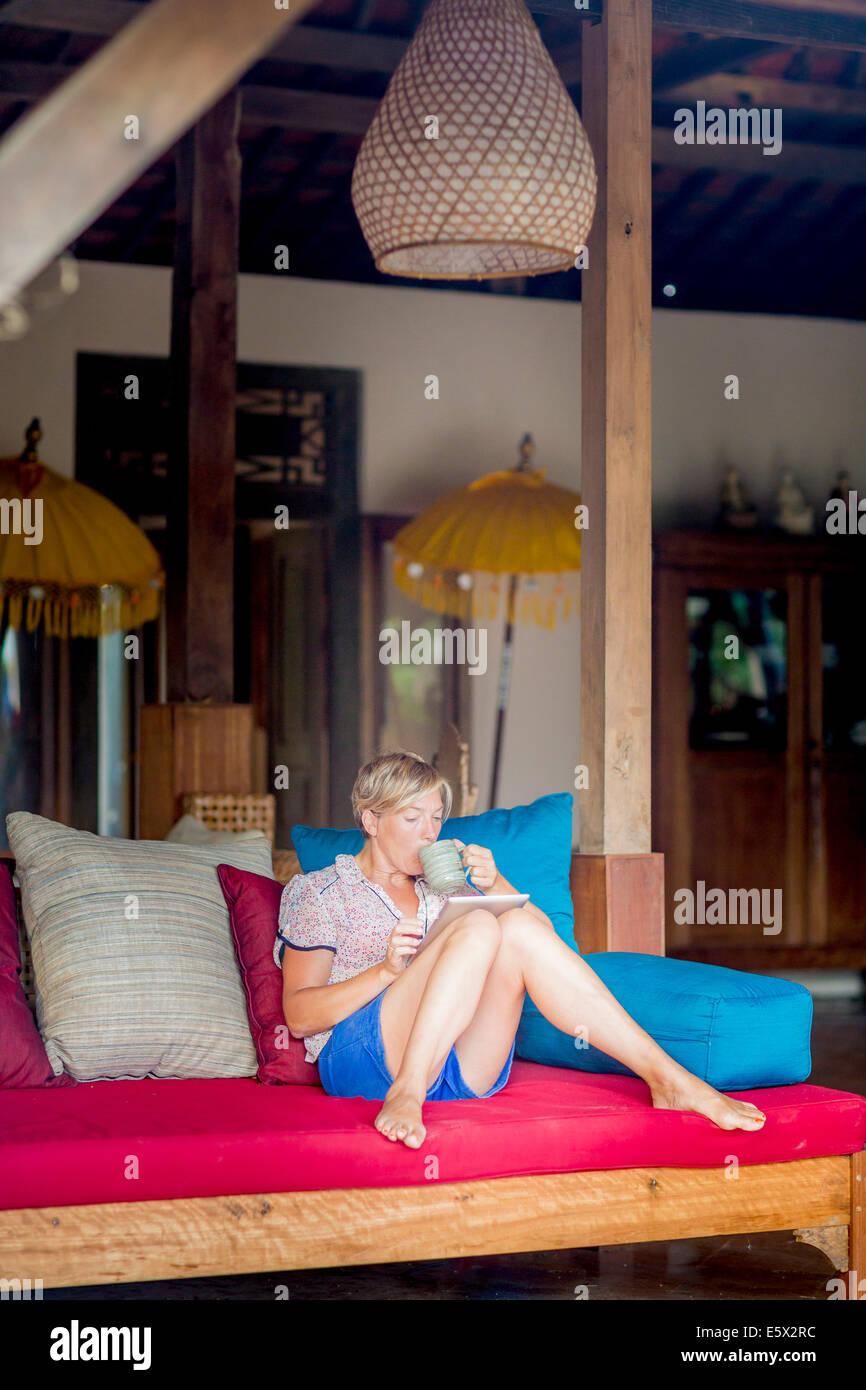 Frau, entspannend, mit Kaffee und digital-Tablette in Urlaub Wohnung Wohnzimmer, Ubud, Bali, Indonesien Stockbild