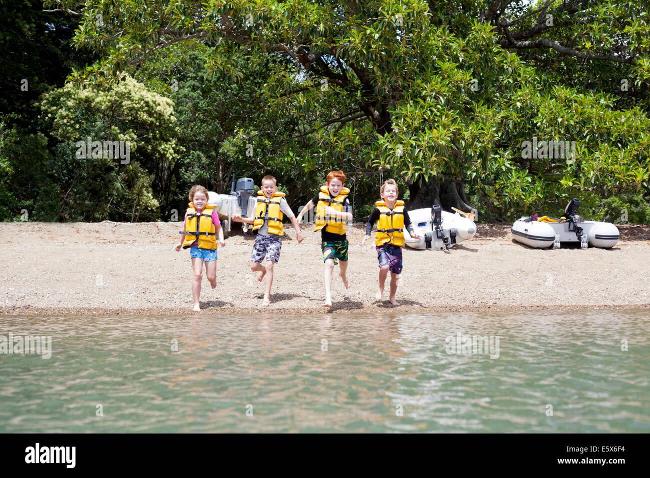 Brüder und Schwester laufen hand in hand ins Meer Stockfoto