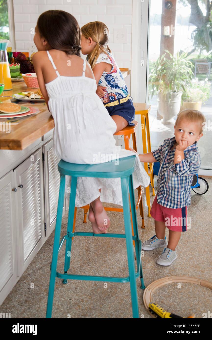 Zwei Schwestern in Küche Frühstücksbar mit Kleinkind Bruder ansehen Stockbild