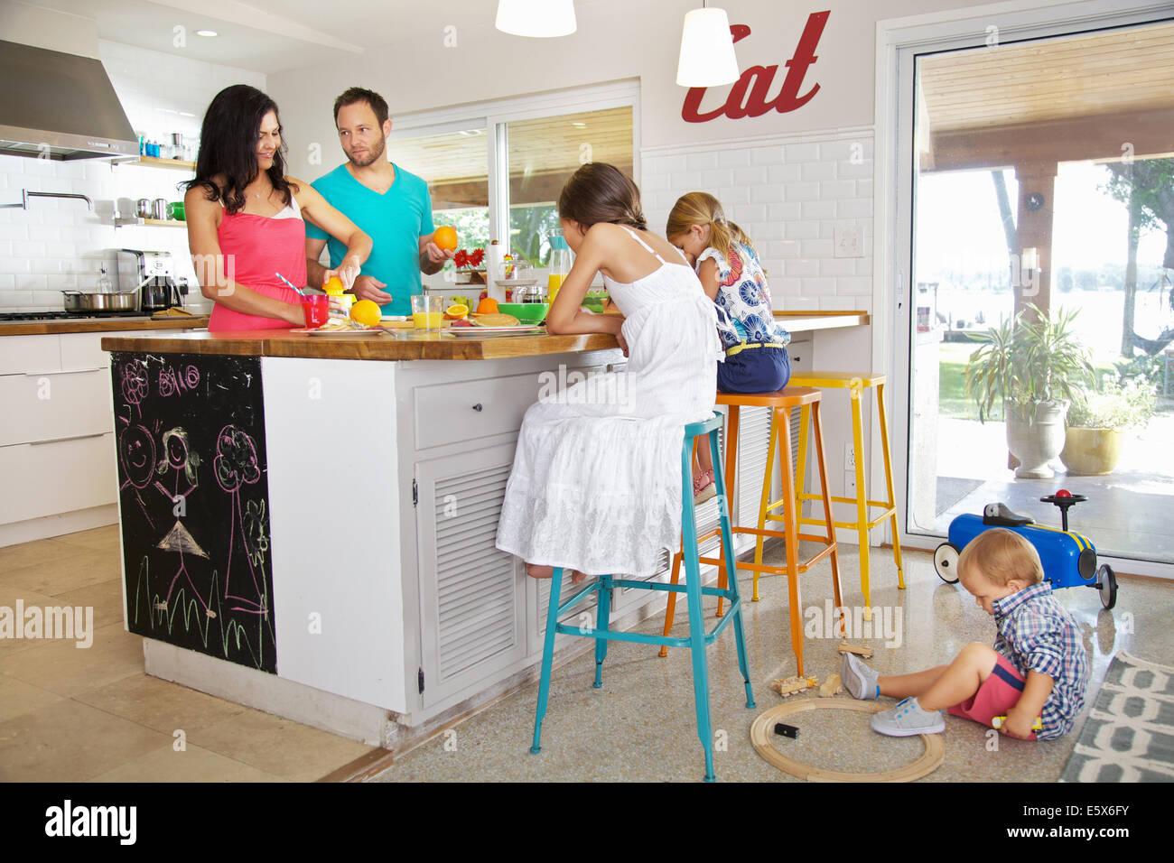 Mitte Erwachsenen Eltern und seinen drei Kindern, die Zubereitung des Frühstücks in der Küche Stockbild