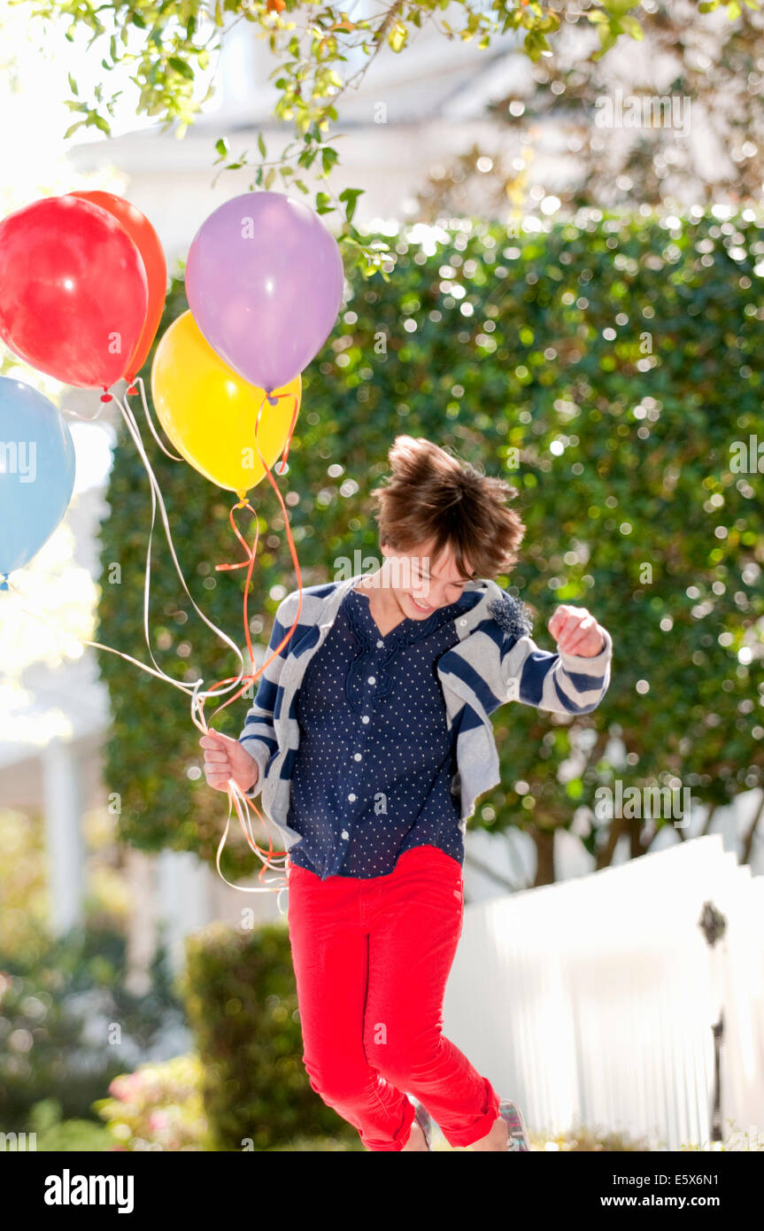 Zehn Jahre altes Mädchen springen aufgeregt mit Haufen Luftballons Stockbild