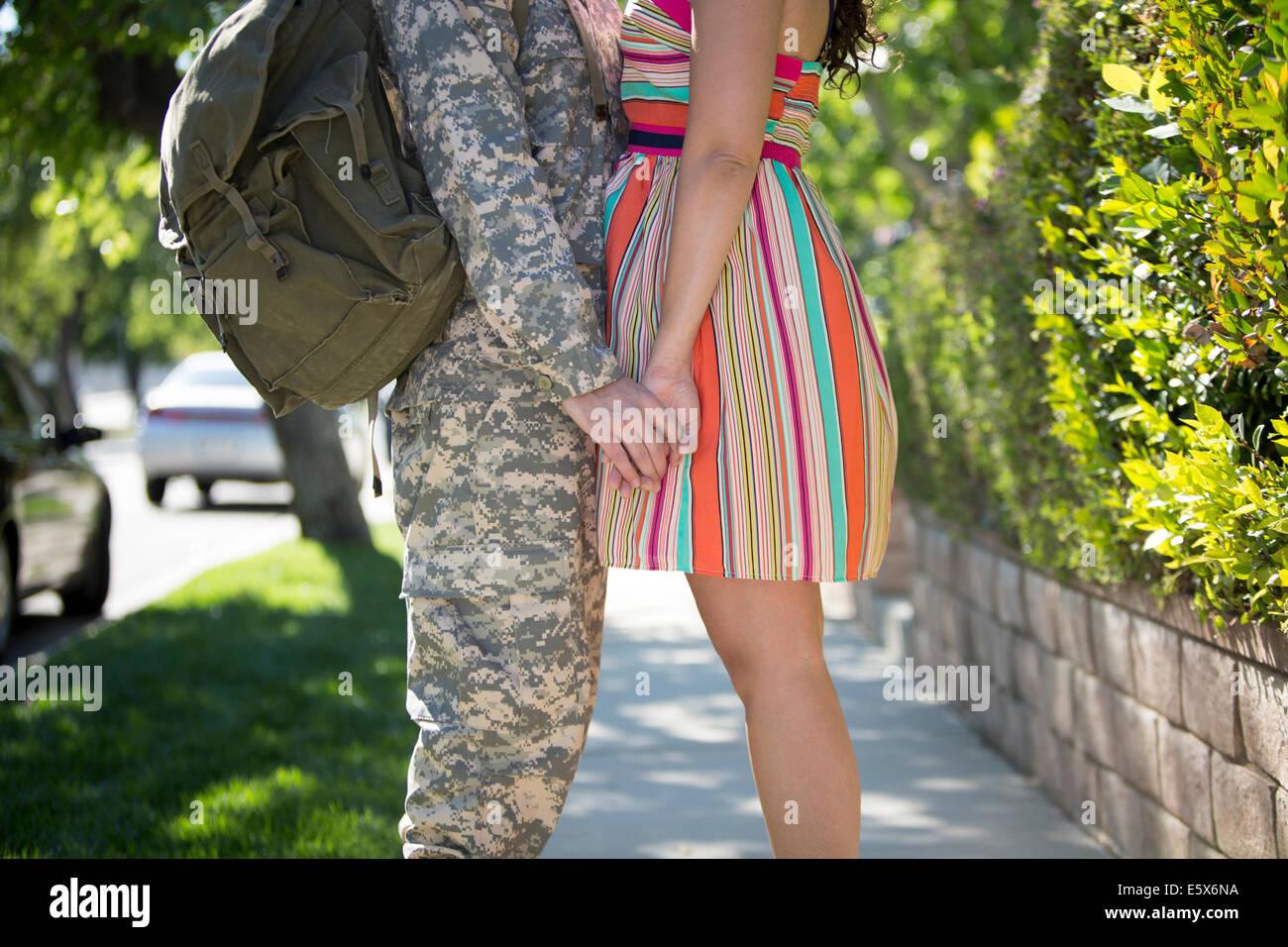 Verkürzte Ansicht des männlichen Soldaten Hand in Hand mit Frau auf der Straße an homecoming Stockbild