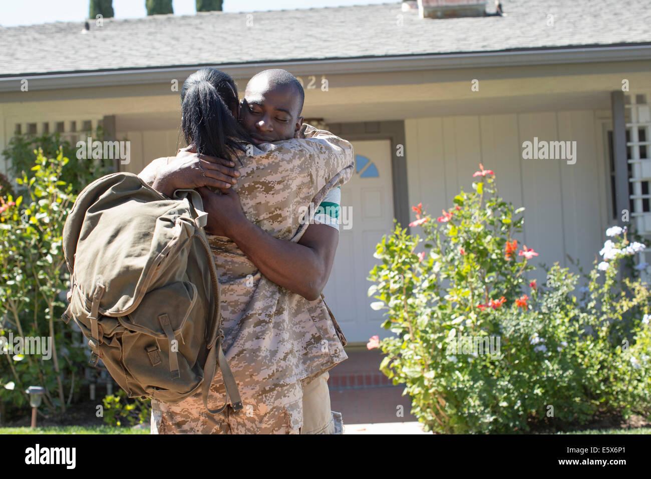 Soldatin umarmt Mann auf Heimkehr Stockbild