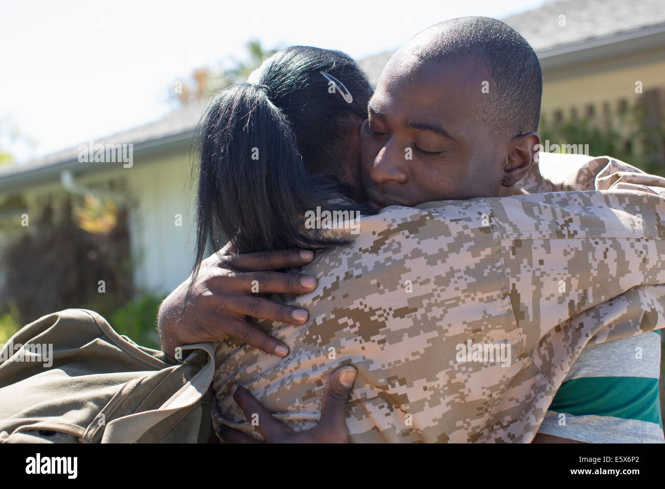 Nahaufnahme von weiblichen Soldaten umarmt Mann auf Heimkehr Stockbild