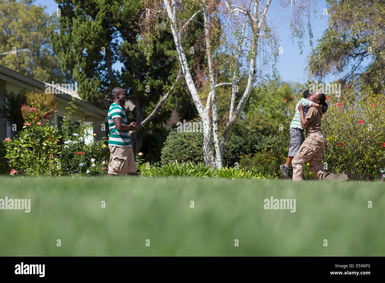 Soldatin umarmt Sohn im Garten auf Heimkehr Stockbild