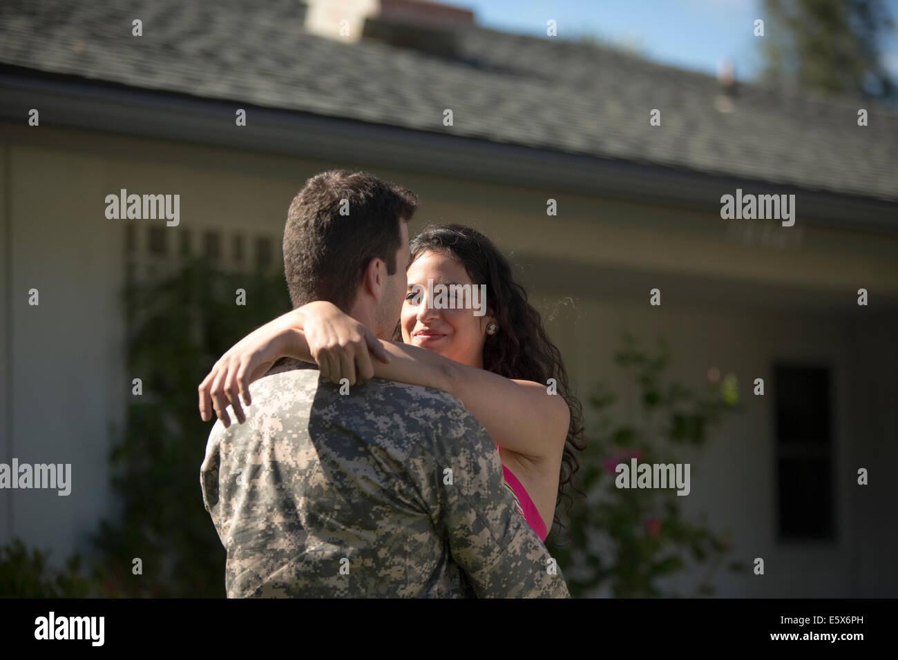 Männlichen Soldaten umarmt Frau im Garten auf Heimkehr Stockbild