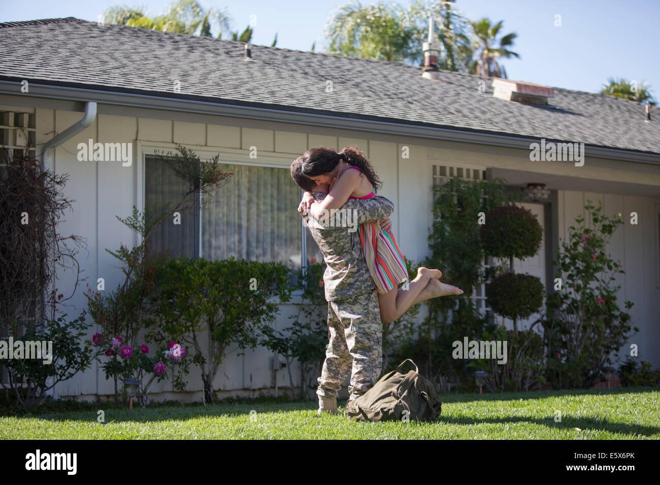 Männlichen Soldaten umarmt und heben Frau im Garten auf Heimkehr Stockbild