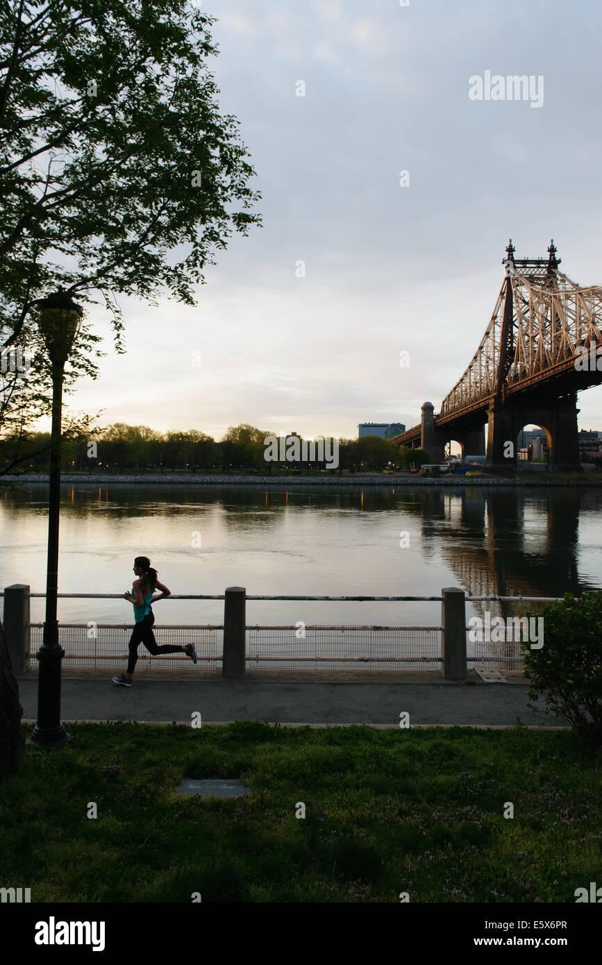 Silhouette der jungen Frau, die auf Wasser, Roosevelt Island, New York City, USA Stockbild
