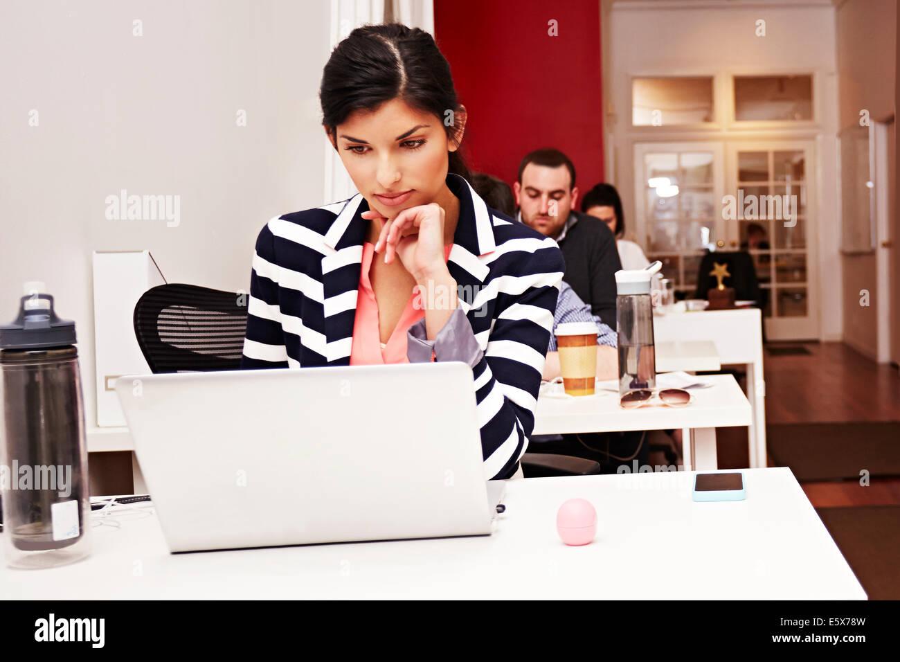 Reihe von Menschen, die auf Laptops im Büro Stockbild