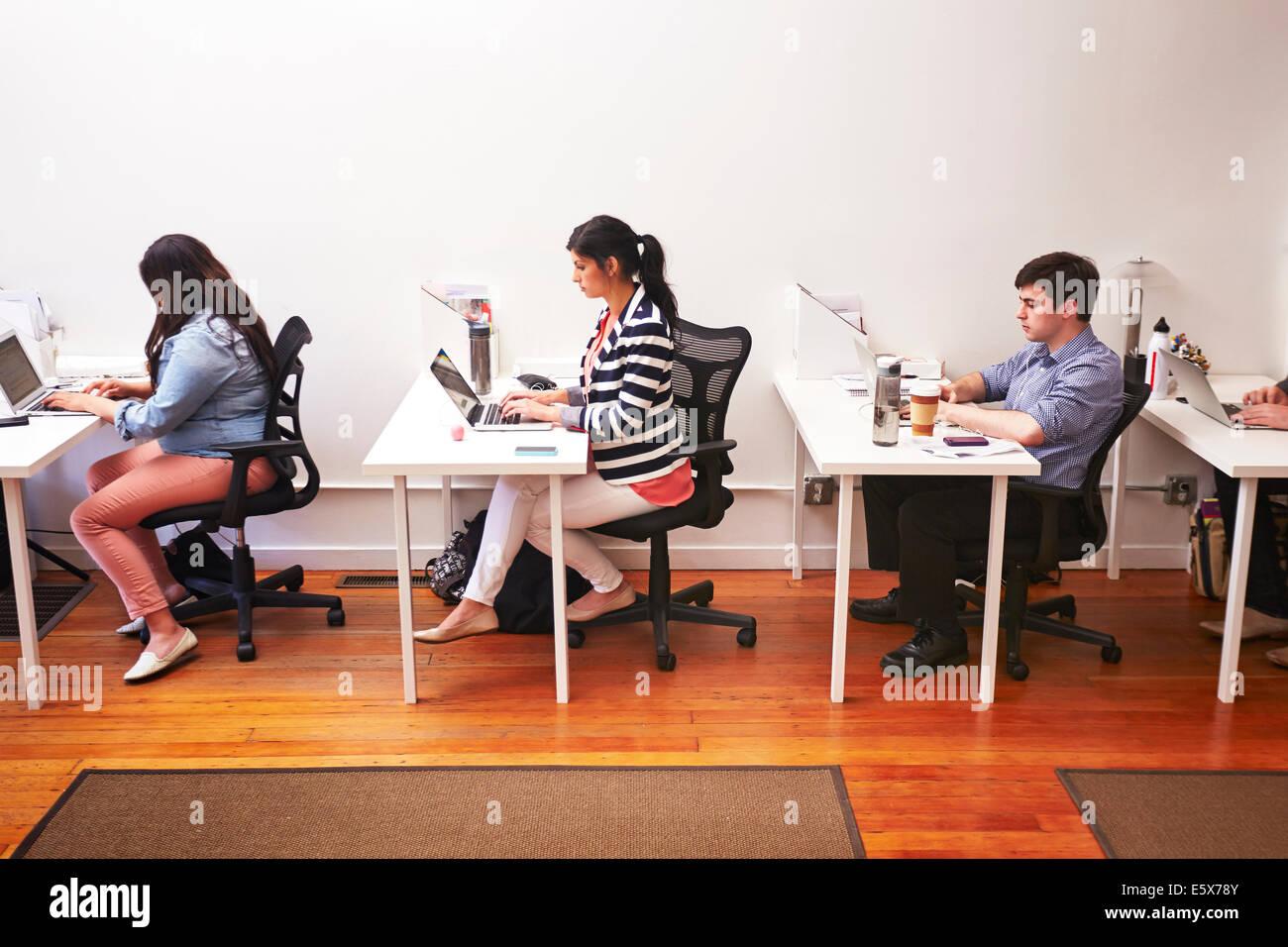 Reihe von Menschen, die Arbeiten am Schreibtisch im Büro Stockbild