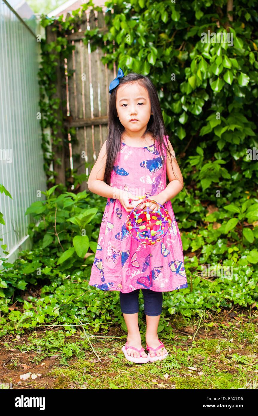 Porträt von Ernst junges Mädchen im Garten mit Spielzeug Stockbild