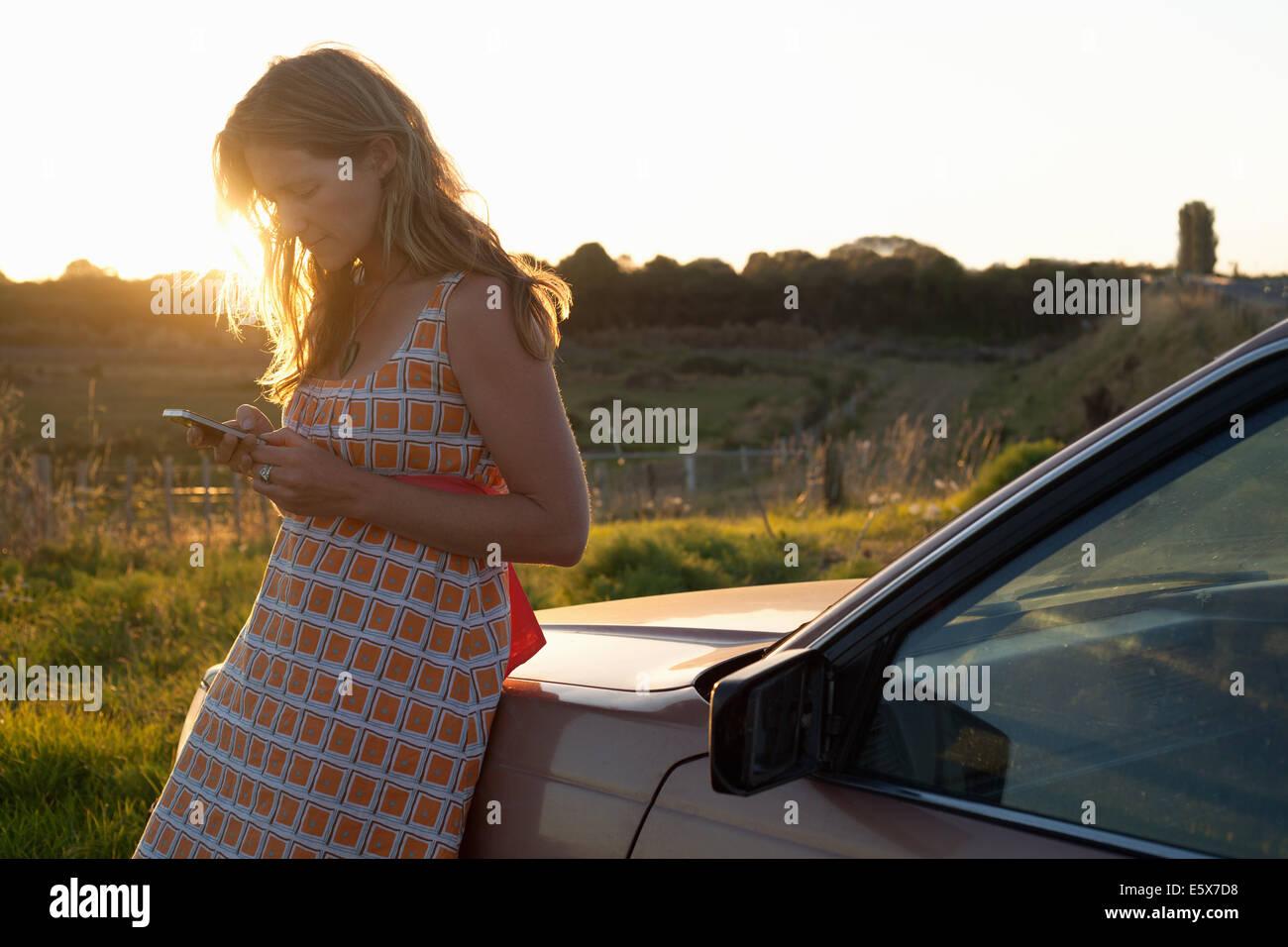 Mitte Erwachsene Frau gelehnt Auto SMS auf smartphone Stockbild