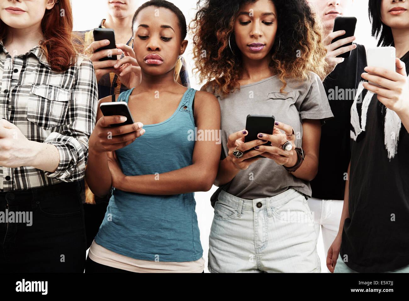 Studioaufnahme von sechs jungen Erwachsenen SMS auf smartphone Stockfoto