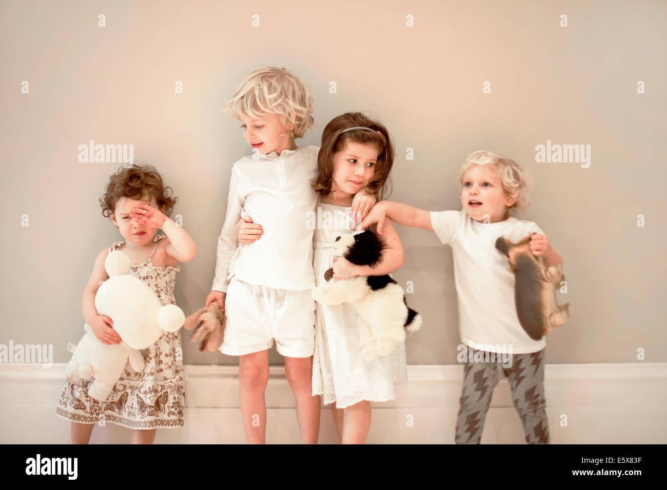 Porträt von vier kleinen Kindern in einer Reihe, man weint Stockbild
