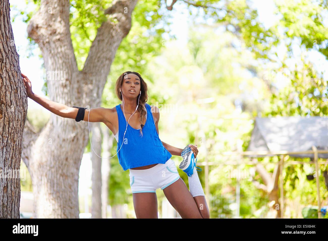 Junge weibliche Läufer Aufwärmen im park Stockbild