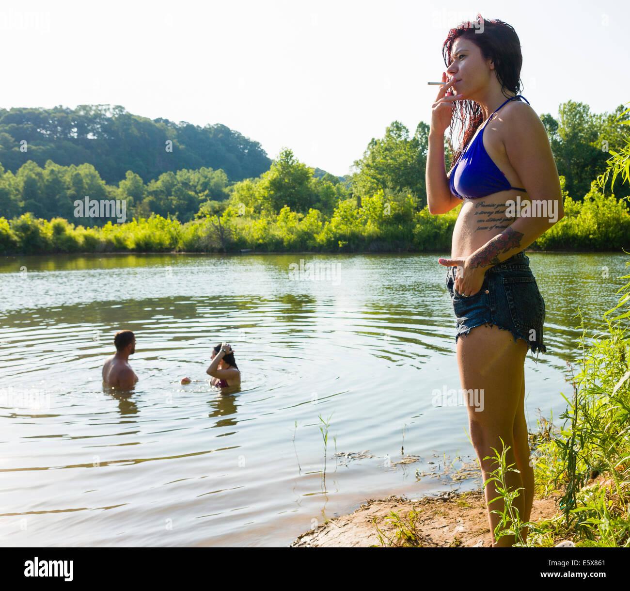 Junge Frau Rauchen Zigarette auf Kanal Bank, Delaware Canal State Park, New Hope, Pennsylvania, USA Stockbild