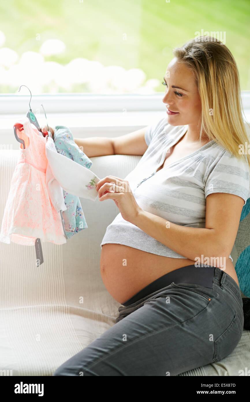 Schwangere Frau betrachten Baby-Kleidung Stockbild