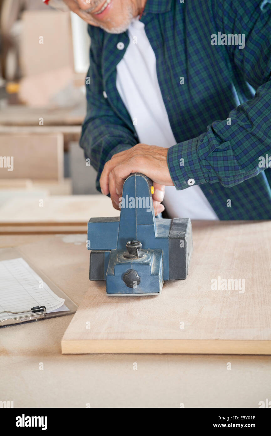 tischler arbeiten mit elektrischen hobel in werkstatt stockfoto
