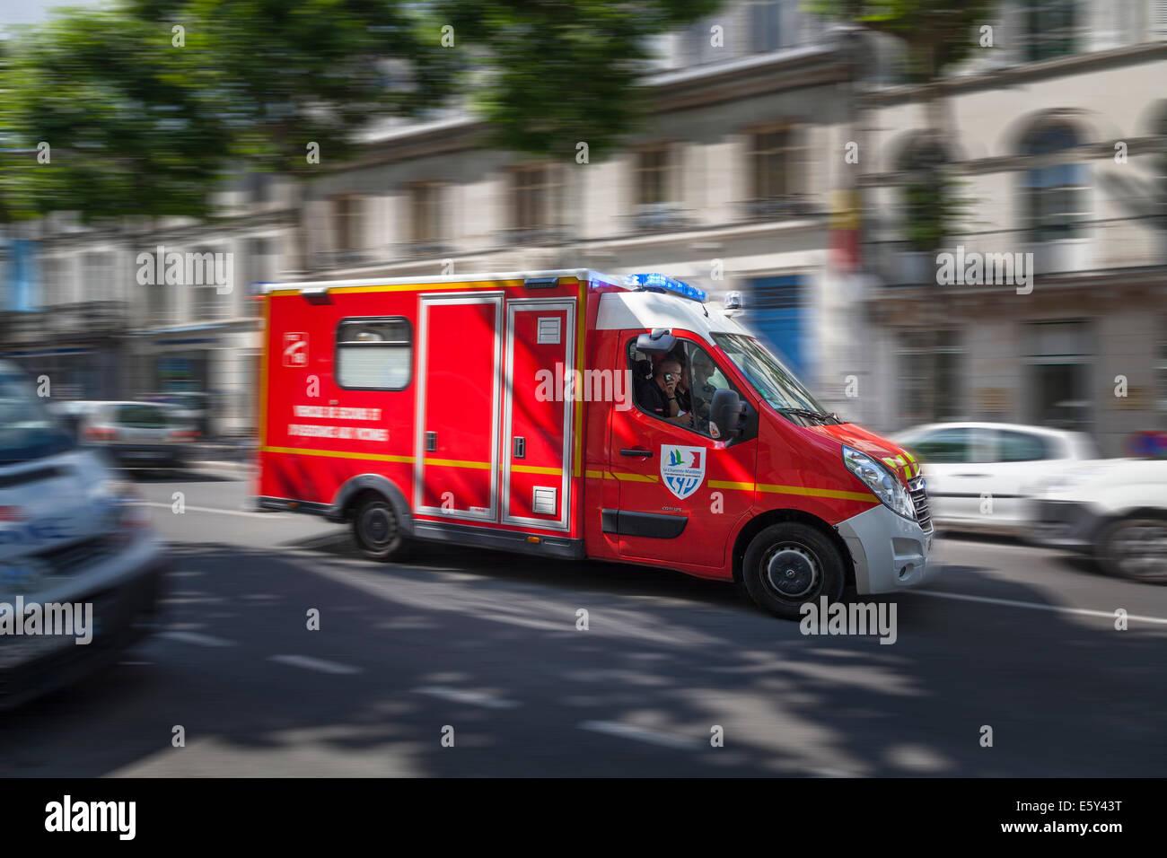 Verschwommene französischen Einsatzfahrzeug Rauschen durch Stadtstraße mit Blaulicht blinkt. Stockbild